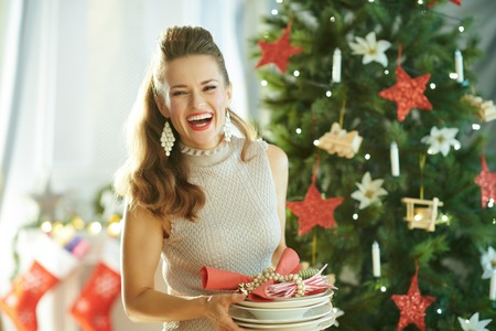 Portrait of smiling young woman with serving plates near Christmas tree