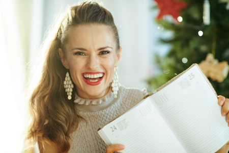 happy trendy housewife near Christmas tree showing diary on the page December 25