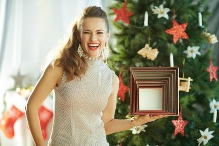 happy young woman near Christmas tree showing Christmas present box Фото со стока - 111299900