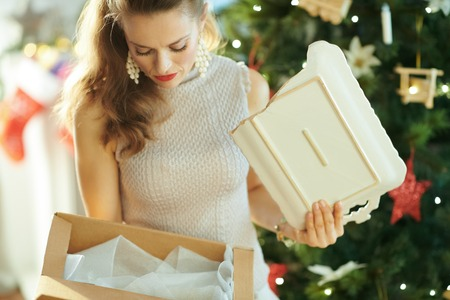 unhappy stylish woman near Christmas tree pulling out a broken dish from the parcel Фото со стока
