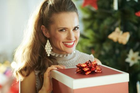 happy stylish woman near Christmas tree opening Christmas present box