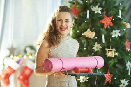 smiling trendy housewife with fitness gear near Christmas tree
