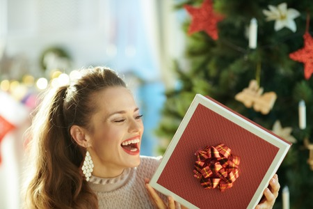 smiling modern woman near Christmas tree looking at Christmas present box