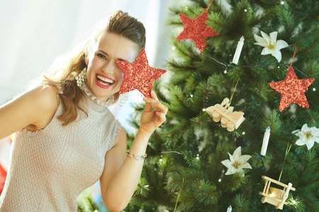 smiling stylish woman playing with Christmas star near Christmas tree 免版税图像
