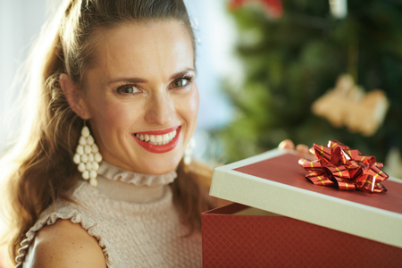 smiling modern housewife near Christmas tree opening Christmas present box