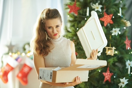 unhappy young woman with a broken dish from the parcel near Christmas tree