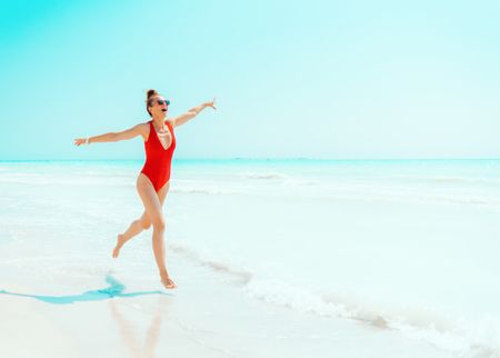 smiling modern woman in red swimwear on the seashore having fun time Banco de Imagens