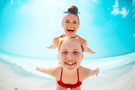 smiling young mother and child in red swimwear on the seashore having fun time