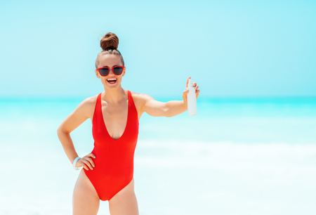 smiling young woman in red swimwear on the beach showing SPF Stock Photo