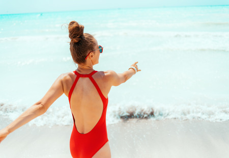 smiling young woman in red beachwear on the beach having fun time 版權商用圖片