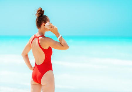 Seen from behind modern woman in red swimwear on the seacoast listening to the sound of the ocean in a shell