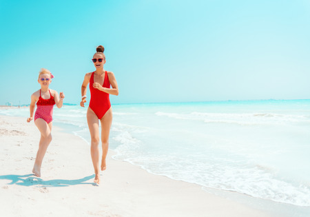 smiling young mother and child in red swimsuit on the seacoast running Фото со стока