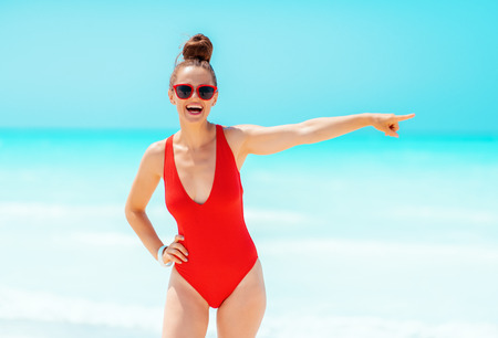 smiling young woman in red beachwear on the seashore pointing at something 版權商用圖片