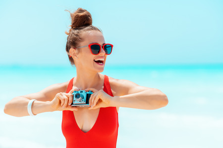 happy young woman in red swimwear with retro photo camera looking into the distance on the seacoast