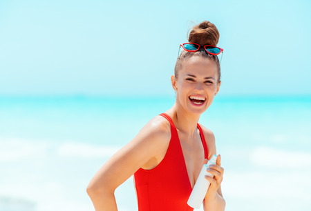 smiling young woman in red beachwear with sun cream on the seacoast