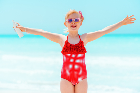 smiling modern girl in red swimwear with sun screen rejoicing on the seacoast