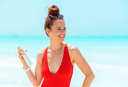 happy modern woman in red swimwear with sun screen on the seashore