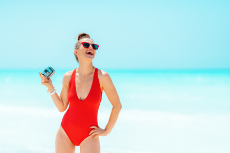 smiling modern woman in red swimsuit with retro photo camera on the beach