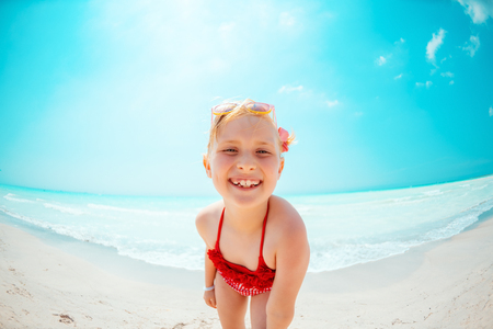 Portrait of smiling modern child in red beachwear on the seacoast