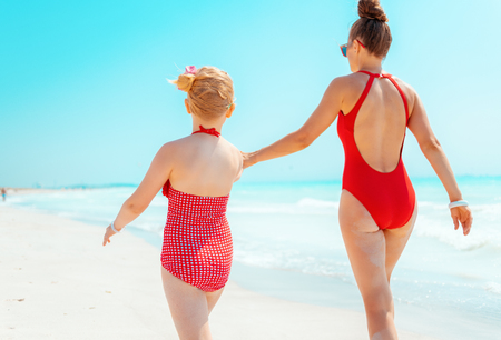Seen from behind young mother and daughter in red swimwear on the seashore walking