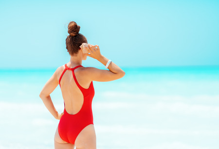 Seen from behind modern woman in red swimsuit on the beach listening to the sound of the ocean in a shell