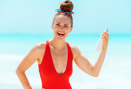happy young woman in red swimsuit with sun screen on the seashore