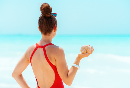 Seen from behind young woman in red swimwear with sea shell on the seacoast