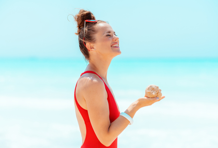 smiling modern woman in red swimsuit with sea shell on the beach Standard-Bild