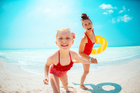 smiling young mother and daughter in red swimsuit with yellow inflatable lifebuoy on the beach Stock Photo