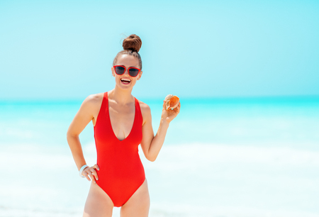 smiling modern woman in red beachwear on the seashore showing a sea shell 版權商用圖片