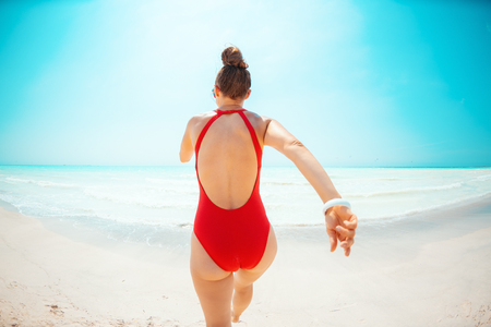 Seen from behind modern woman in red beachwear on the seashore jogging Stock Photo