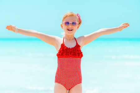 happy modern child in red swimsuit on the seashore rejoicing