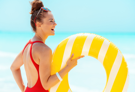 happy modern woman in red beachwear with yellow inflatable lifebuoy looking into the distance on the beach 版權商用圖片