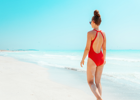 Seen from behind modern woman in red swimsuit on the seacoast walking