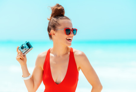 smiling young woman in red beachwear with retro photo camera looking aside on the beach