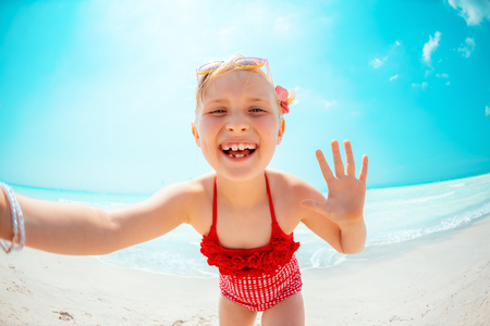 happy modern child in red beachwear on the seacoast taking selfie