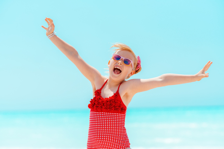 smiling modern child in red beachwear on the beach rejoicing Stock Photo