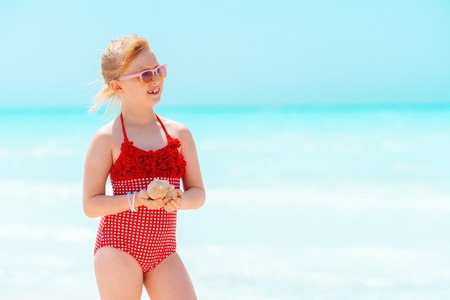 happy modern girl in red swimsuit with seashell looking into the distance on the beach 版權商用圖片