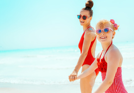smiling young mother and child in red swimsuit on the beach walking