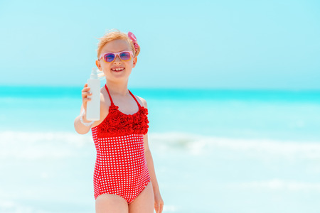 smiling modern girl in red swimsuit on the seacoast showing suntan lotion Stock Photo