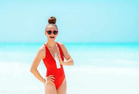 smiling young woman in red swimsuit on the beach showing sun screen
