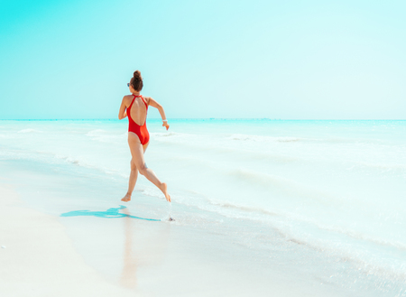 Seen from behind modern woman in red beachwear on the seashore jogging 版權商用圖片