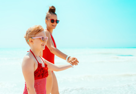smiling modern mother and child in red beachwear on the seacoast walking