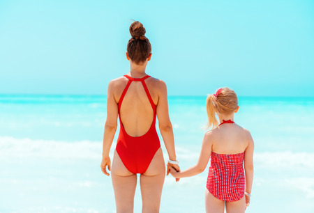 Seen from behind modern mother and daughter in red beachwear standing on the seacoast