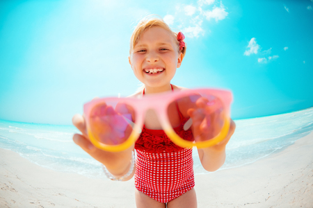 smiling modern girl in red beachwear on the beach showing sunglasses