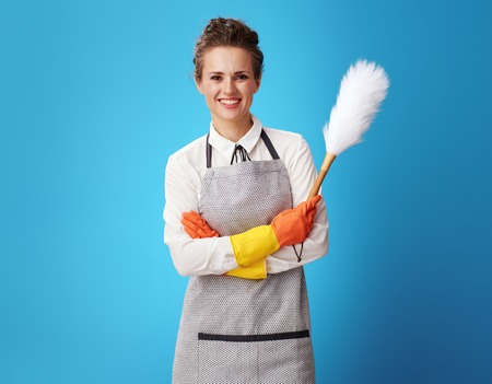 Portrait of happy young cleaning woman in apron with dust cleaning brush isolated on blue. special uniform and professional equipment for cleaning, willingness to work - all this for the best customer Stock fotó