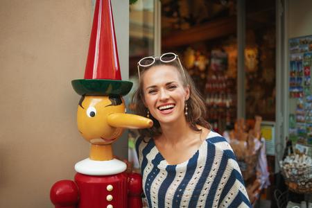 Pisa - August, 3, 2018: Portrait of smiling woman near the tourist souvenir shop in Pisa, Italy Stock Photo