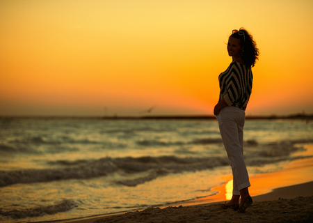 Full length portrait of modern woman on the seashore in the evening. How to become happy? Just stroll along the seashore on a summer evening. Stockfoto