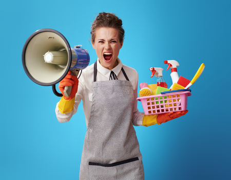 angry young cleaning lady in apron with a basket with cleansers and brushes shouting through a megaphone on blue background. Professional cleaner says - save your time! Order cleaning service!