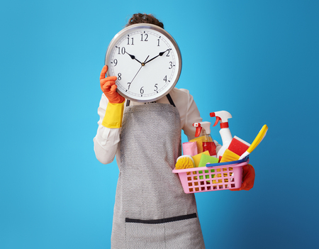 cleaning woman in apron with basket with detergents holding clock in front of face against blue background. Time is money! If cleaning is not in the business plan, you should call a cleaning service.